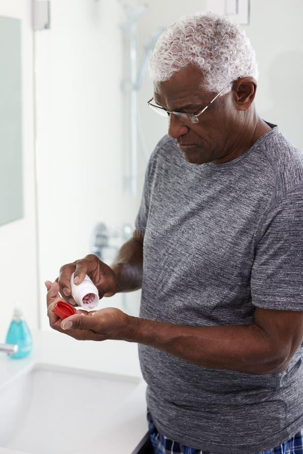 Hogere Mens in Badkamersspiegel die Pyjama's dragen die de Tablet van het Vitaminesupplement nemen stock fotografie