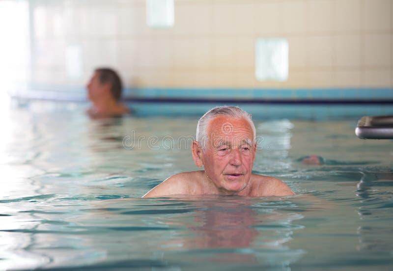 Hogere mens bij rand van zwembad stock fotografie