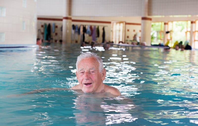 Hogere mens bij rand van zwembad stock afbeeldingen
