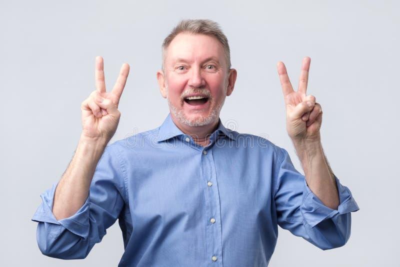 Hogere mens in blauw overhemd die overwinningsteken tonen stock afbeelding