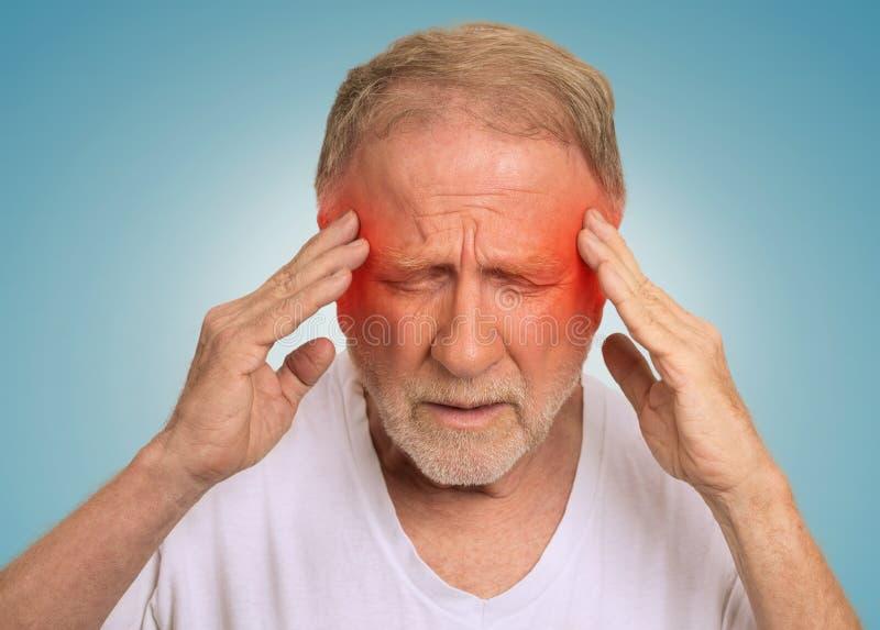 Hogere mens die aan hoofdpijnhanden lijden op hoofd stock afbeeldingen
