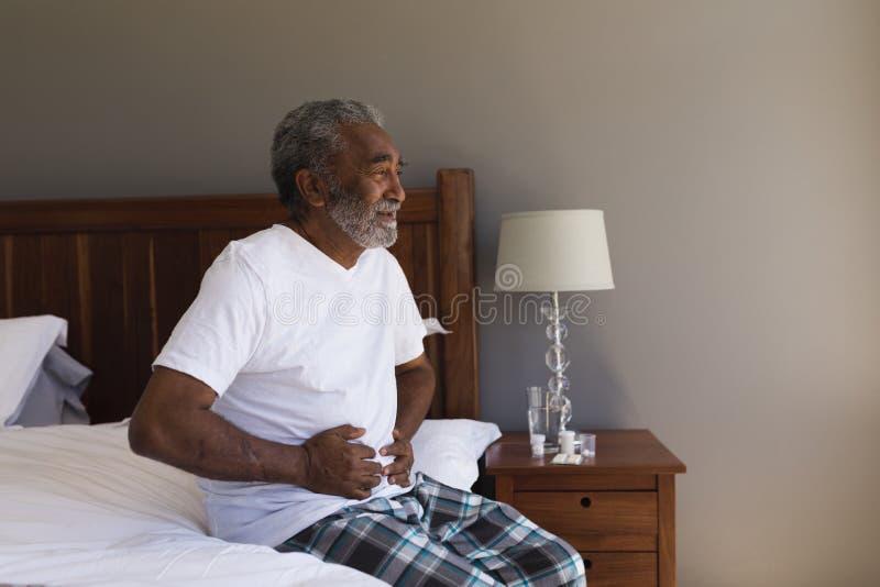 Hogere mens die aan maagpijn lijden in slaapkamer royalty-vrije stock foto
