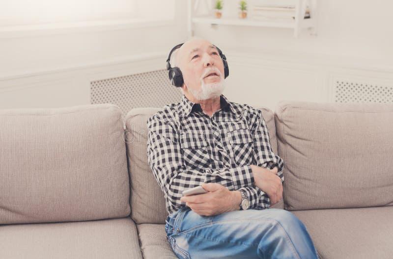 Hogere mens die aan muziek met hoofdtelefoons luisteren royalty-vrije stock afbeelding