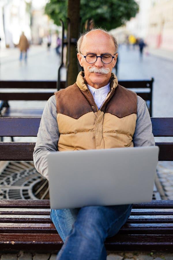 Hogere mens die aan zijn laptop zitting op de bank in de stadsstraat werken royalty-vrije stock foto's