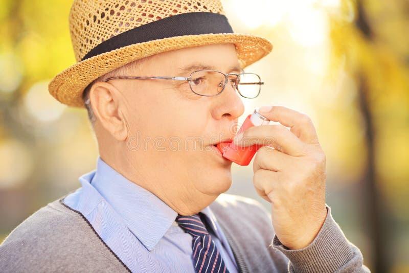 Hogere mens die astmabehandeling in een park neemt stock fotografie
