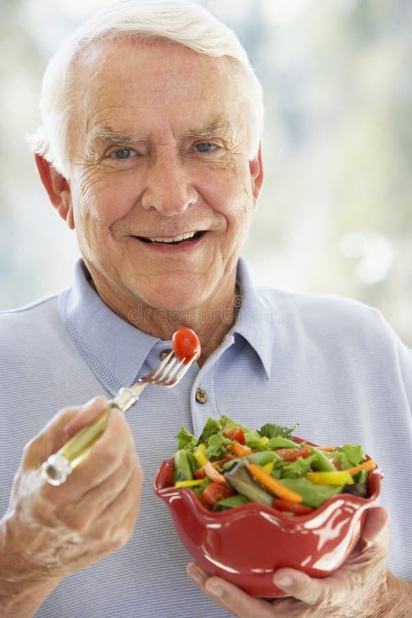 Hogere Mens die bij Camera glimlacht en Salade eet royalty-vrije stock afbeeldingen