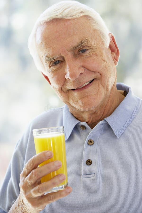 Hogere Mens die bij Camera glimlacht en Salade eet stock afbeeldingen