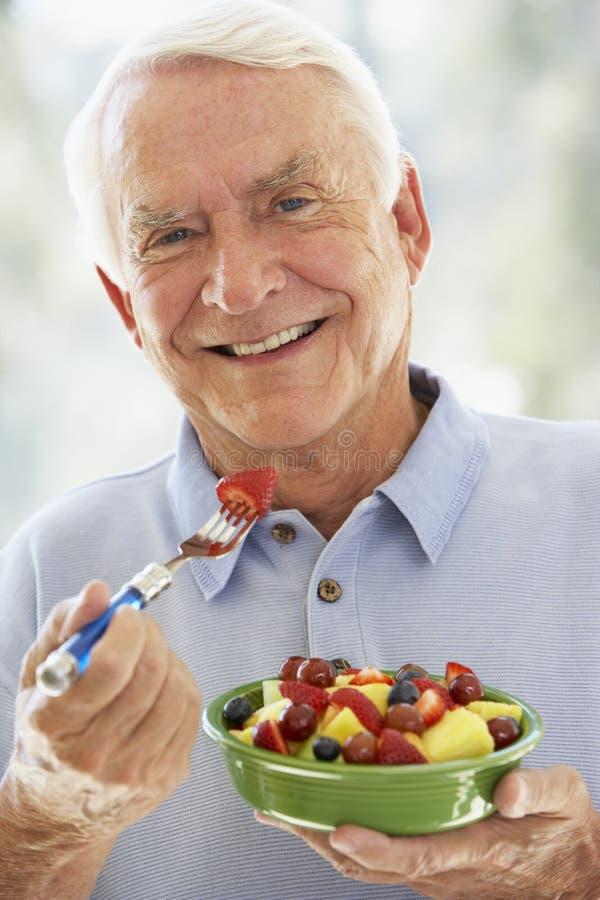 Hogere Mens die bij Camera glimlacht en Salade eet stock foto