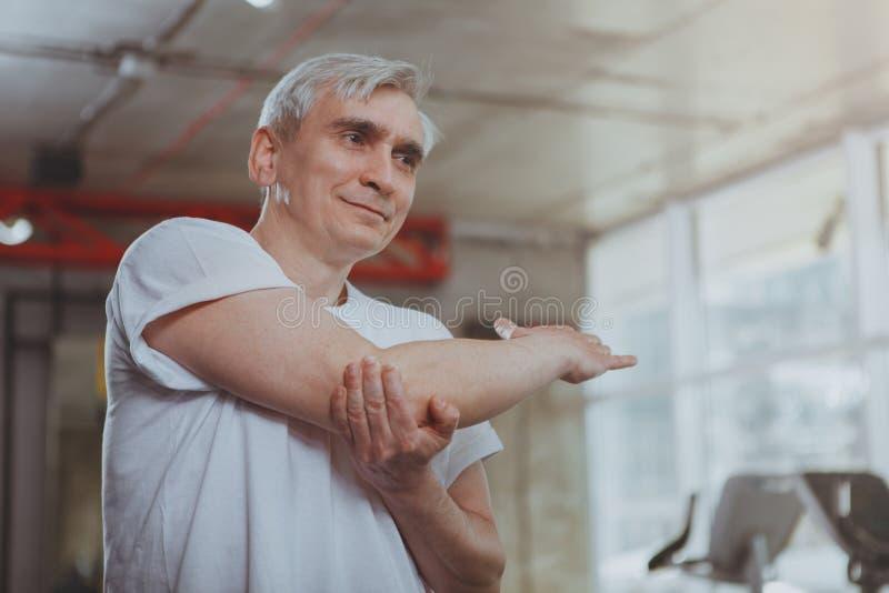 Hogere mens die bij de gymnastiek uitwerken stock afbeelding
