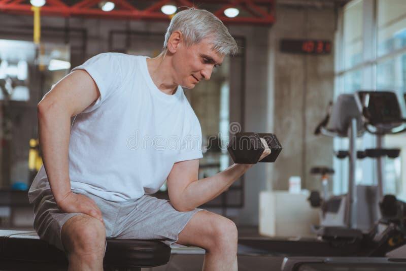 Hogere mens die bij de gymnastiek uitwerken stock foto