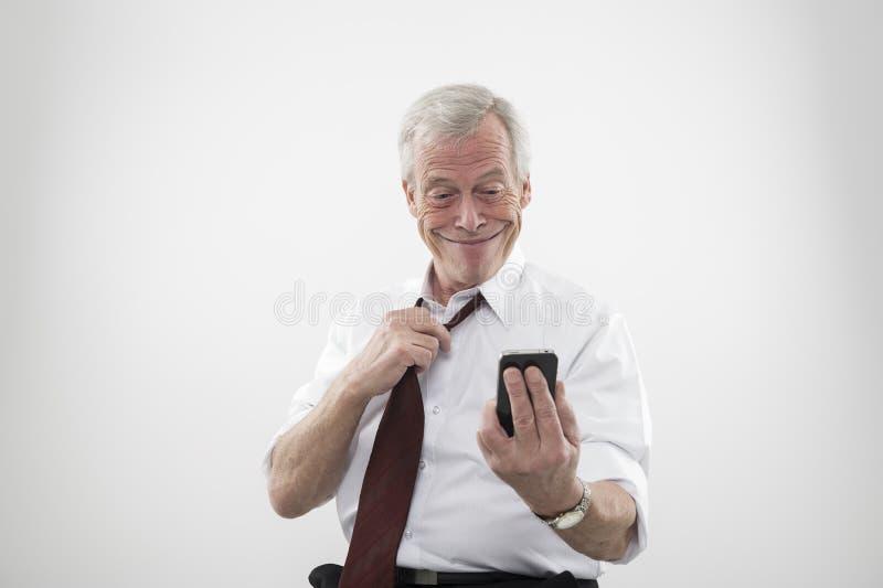 Hogere mens die bij een mobiele telefoon glimlacht stock afbeeldingen