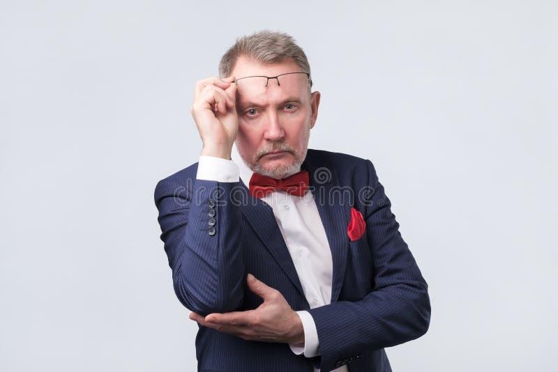 Hogere mens die in blauw kostuum zeker kijken stock fotografie
