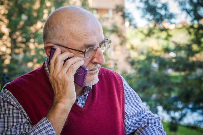 Hogere Mens die de Telefoon van de Cel met behulp van stock foto's