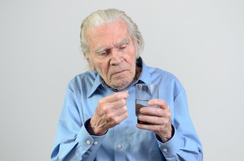Hogere mens die de voorgeschreven dosis geneeskunde nemen stock afbeelding