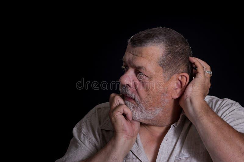 Hogere mens die desperately over het levensproblemen denken in de duisternis stock foto's