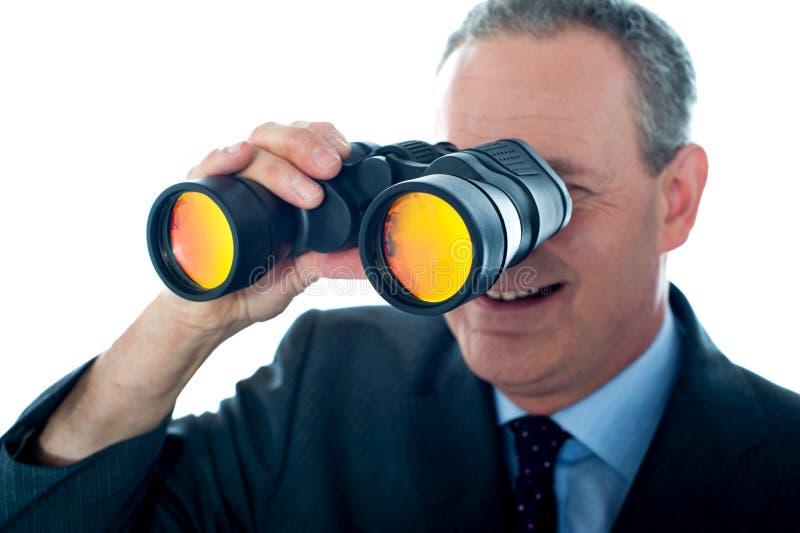 Hogere mens die door verrekijkers waarneemt royalty-vrije stock fotografie