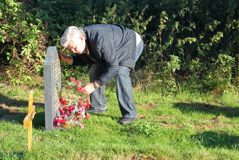 Hogere mens die in een begraafplaats rouwen. royalty-vrije stock foto