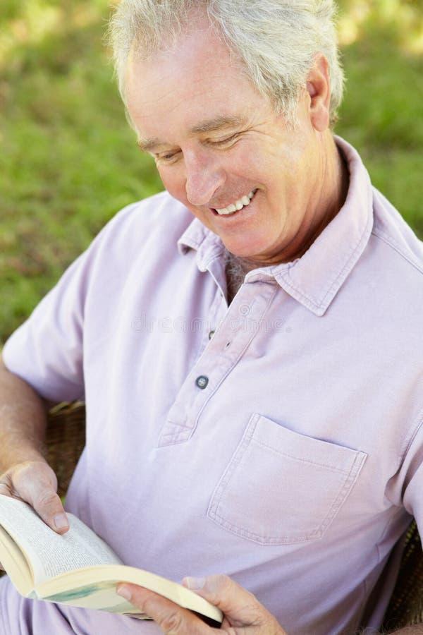 Hogere mens die een boek leest stock afbeelding