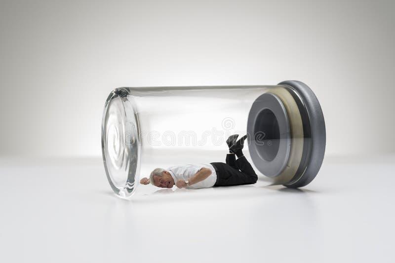 Hogere mens die in een glaskruik wordt opgesloten stock fotografie