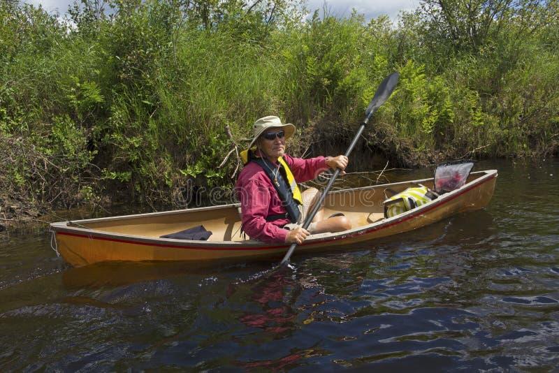 Hogere mens die een kleine kano op de Amerikaanse elandenrivier paddelen stock afbeeldingen