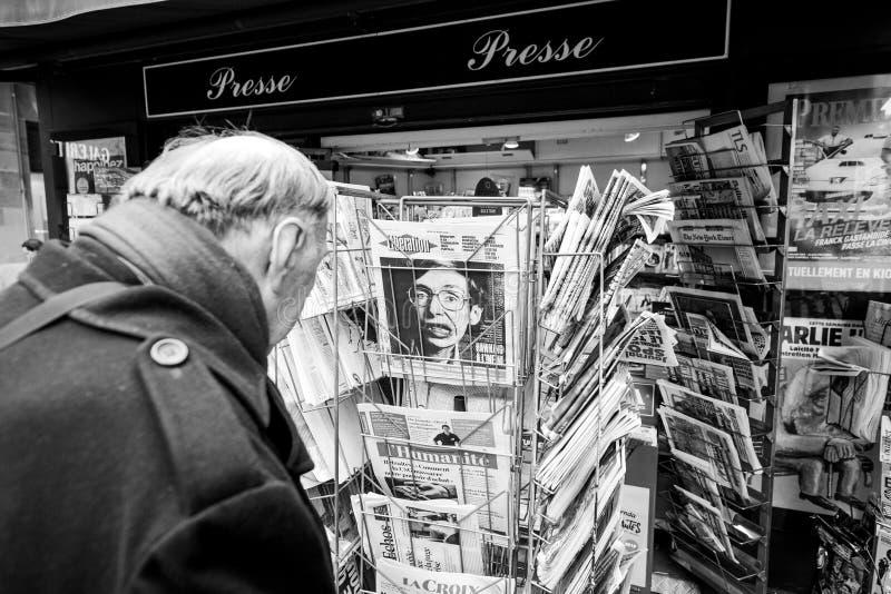 Hogere mens die Franse krantenbevrijding kopen bij Parijse pers stock afbeeldingen
