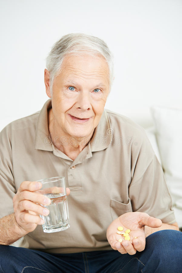Hogere mens die geneeskunde met water nemen stock fotografie
