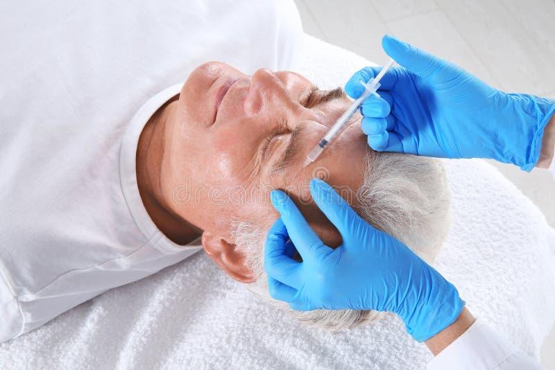 Hogere mens die gezichtsinjectie in kliniek krijgen royalty-vrije stock afbeelding
