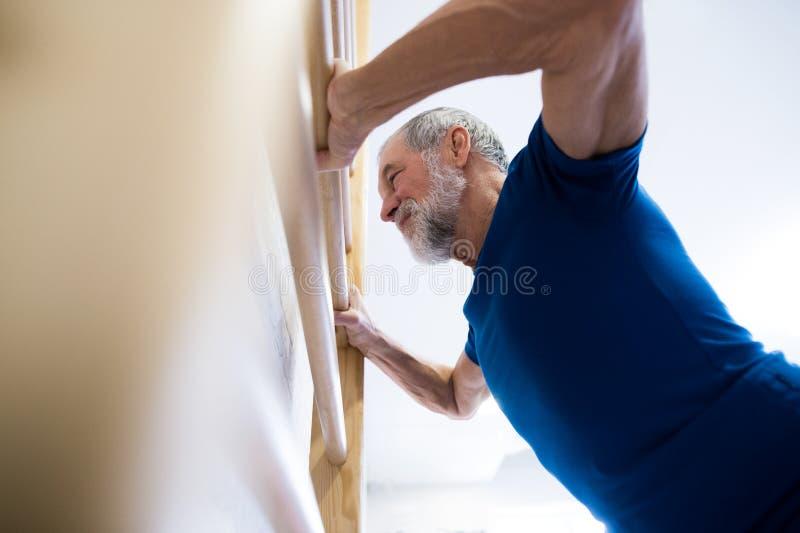 Hogere mens die in gymnastiek op muurbars uitoefenen royalty-vrije stock foto's