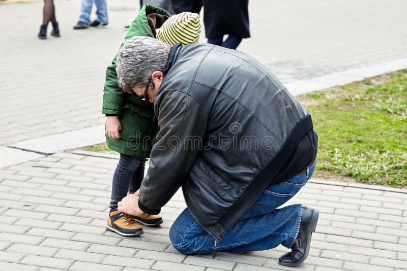 Hogere mens die het kant op een kindlaarzen binden De vader of de grootvader helpen zijn kleine zoon of kleinzoon Beide toevallig royalty-vrije stock foto's