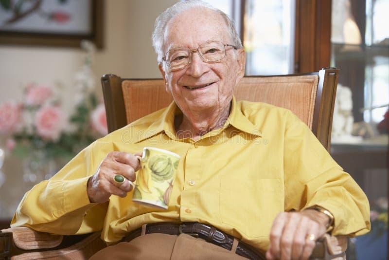 Hogere mens die hete drank drinkt stock fotografie