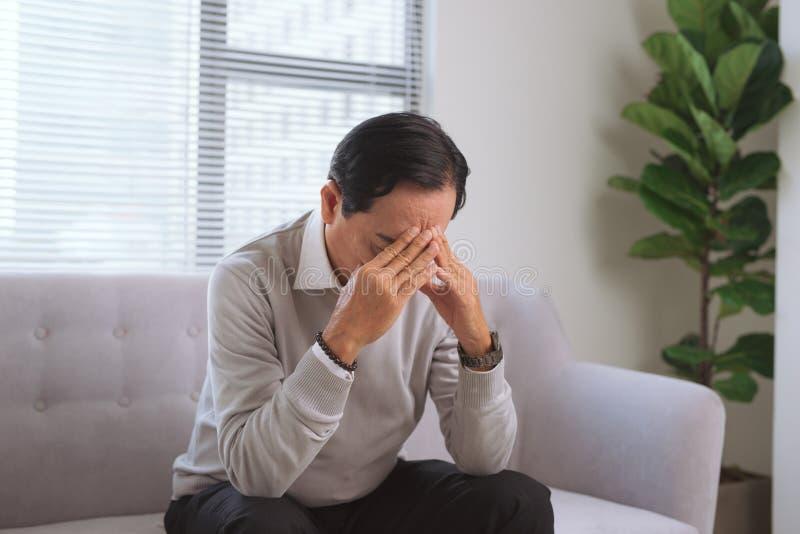 Hogere mens die hoofdpijn hebben terwijl thuis het zitten op laag royalty-vrije stock foto's