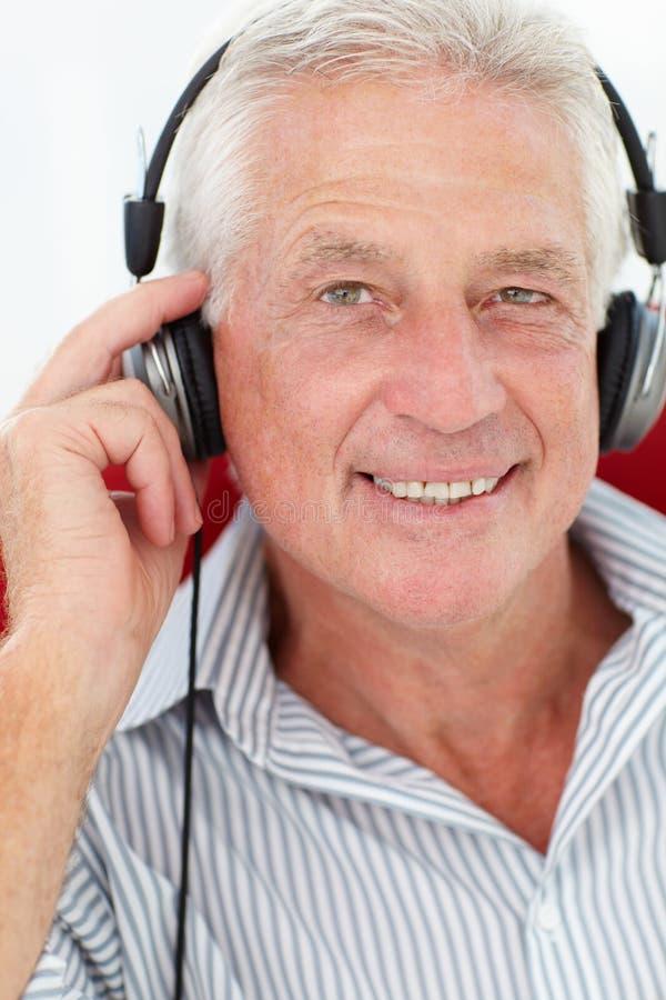 Hogere mens die hoofdtelefoons draagt stock foto's