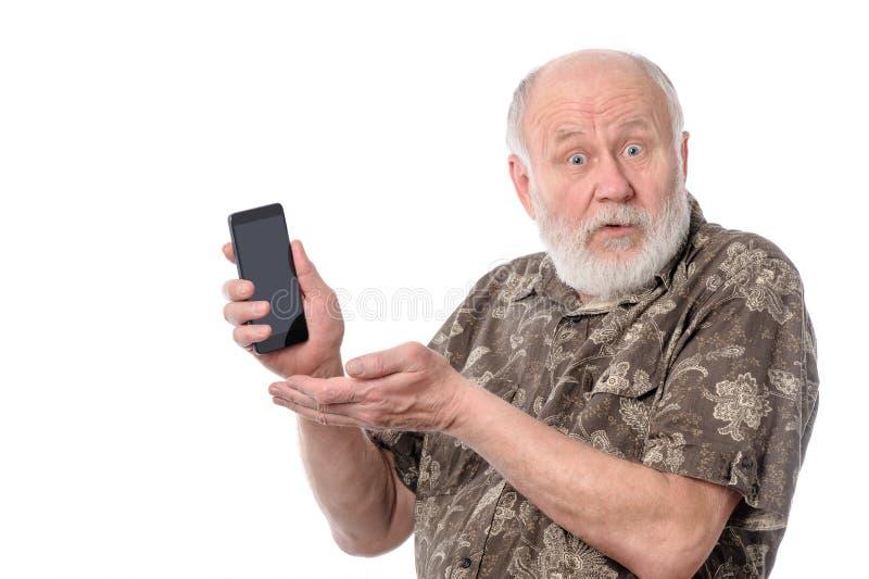 Hogere mens die iets tonen die bij het smartphonescherm, op wit wordt geïsoleerd stock foto's