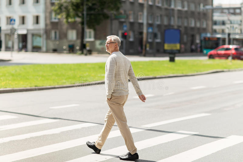 Hogere mens die langs stadszebrapad lopen royalty-vrije stock foto's