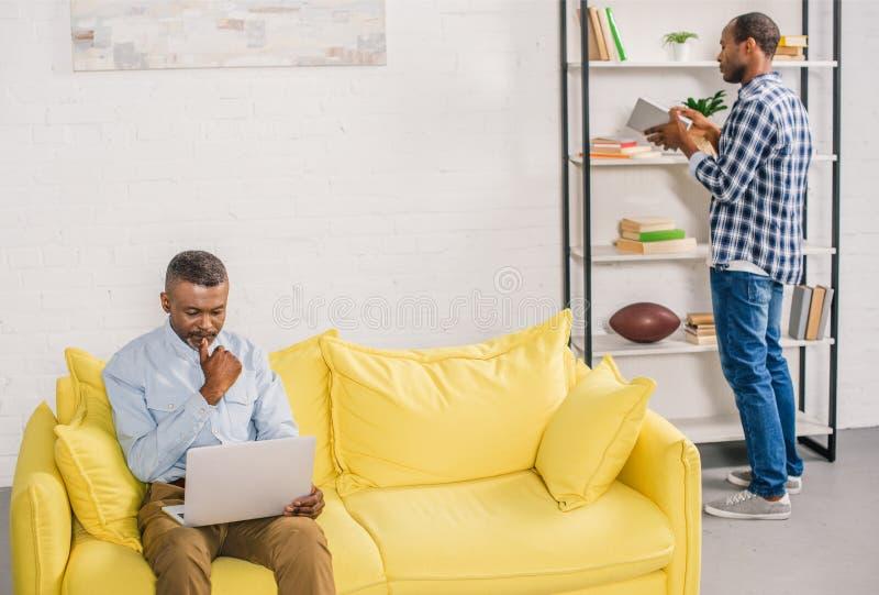 hogere mens die laptop met behulp van terwijl het volwassen boek van de zoonsholding dichtbij boekenrekken royalty-vrije stock foto's