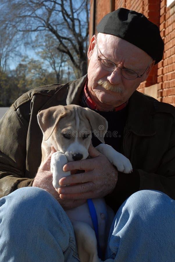 Hogere mens die leuk puppy houdt royalty-vrije stock afbeeldingen
