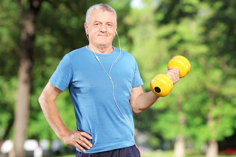 Hogere mens die met gewicht in park uitoefenen stock afbeelding