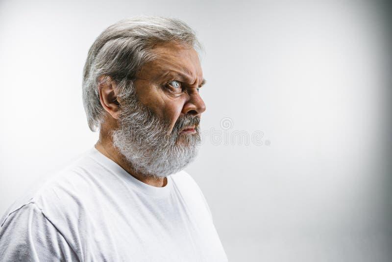 Hogere mens die met weerzinwekkende uitdrukking iets op wit afwijzen royalty-vrije stock foto's