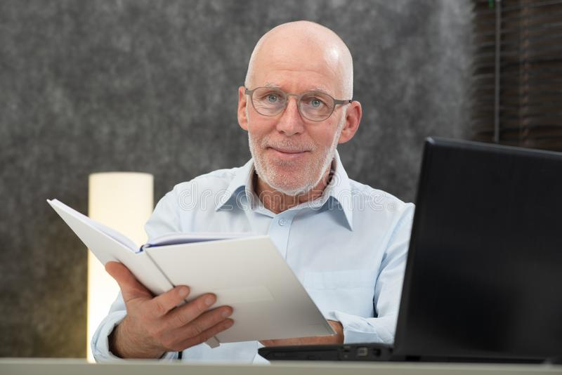Hogere mens die met witte haren en glazen boek lezen royalty-vrije stock afbeelding