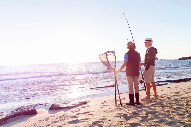 Hogere mens die met zijn kleinzoon vissen royalty-vrije stock fotografie