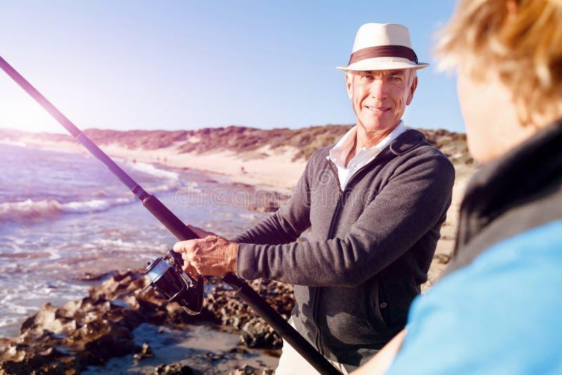 Hogere mens die met zijn kleinzoon vissen royalty-vrije stock afbeelding