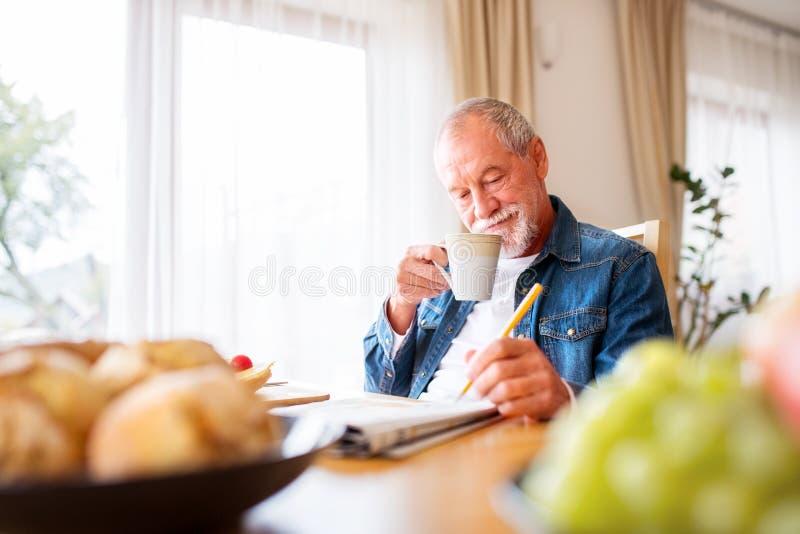 Hogere mens die ontbijt eten en kruiswoordraadsels thuis doen stock fotografie