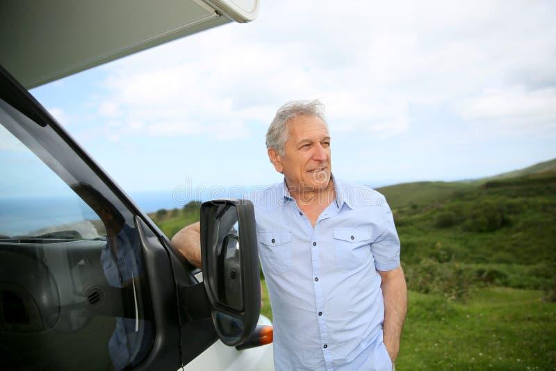 Hogere mens die op het kamperen auto leunen royalty-vrije stock foto