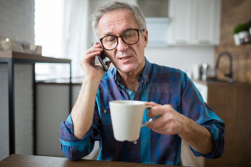 Hogere mens die op mobiel in keuken spreken stock fotografie