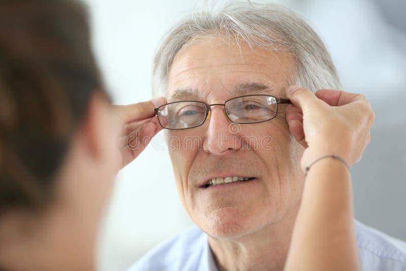 Hogere mens die op nieuwe oogglazen proberen stock afbeelding