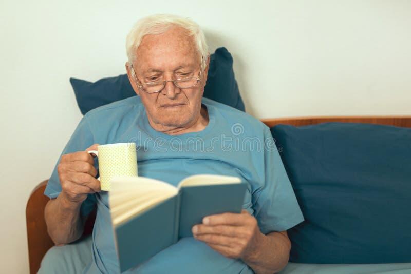 Hogere mens die op slecht en het lezen boek liggen stock afbeeldingen