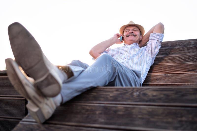 Hogere mens die op telefoon het rusten spreken stock fotografie