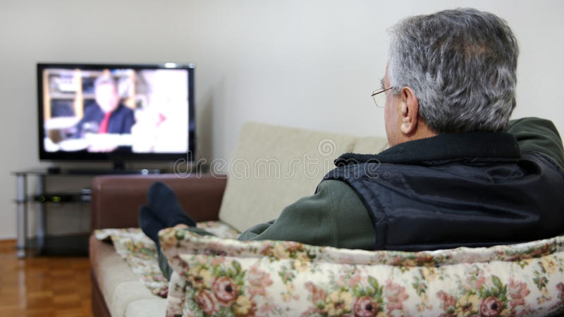 Hogere mens die op TV letten royalty-vrije stock foto