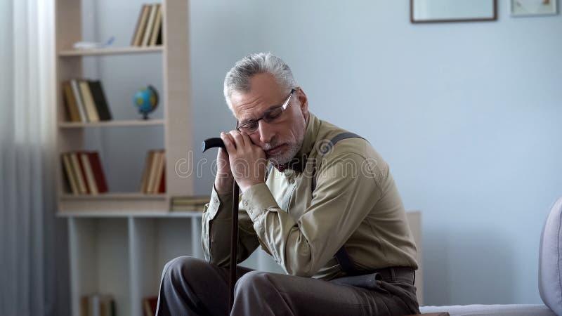 Hogere mens die op wandelstok leunen, die dutje, het goed van de middagslaap voor gezondheid nemen royalty-vrije stock afbeeldingen