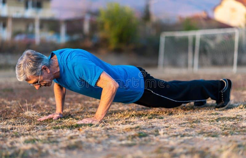 Hogere Mens die opdrukoefeningen op een training doen royalty-vrije stock afbeelding